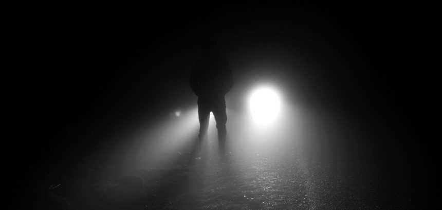 A figure standup in front of headlight and foggy